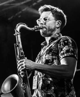 A black and white picture of a man with short hair, wearing glasses and a exotic floral t-shirt playing the saxophone. Working as a music workshop leader.