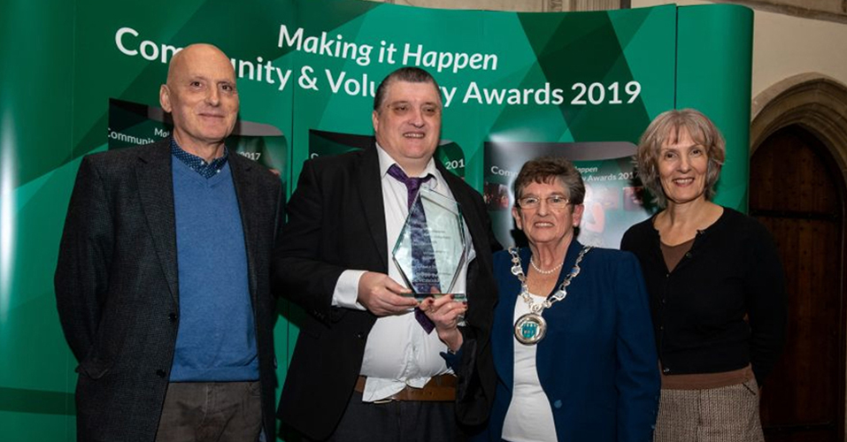 A group picture consisting of 4 people, two of which are Sue Marlow and Nigel Reed. They are at the Making it Happen Community & Voluntary Awards 2019 Sevenoaks, collecting their award for Equality.
